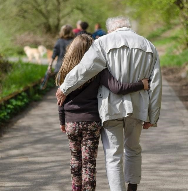 An elderly man walking with a young female child; presumably a grandparent and grandchild